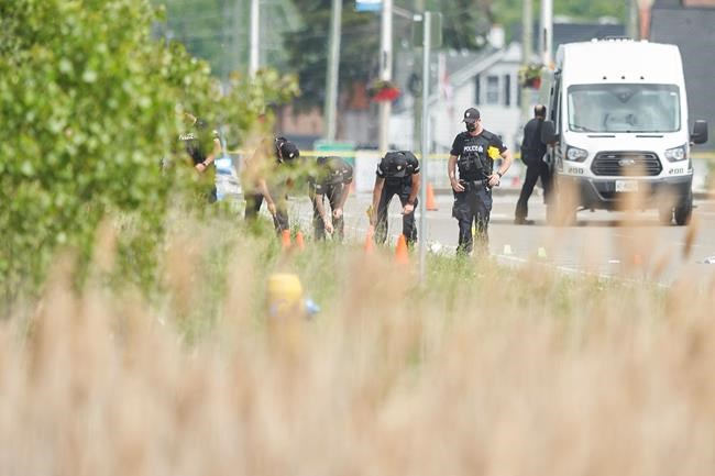 A line of police officers look for evidence at the scene of a car crash in London, Ont., on Monday, June 7, 2021. London police in London say four people have died after several pedestrians were struck by a car Sunday night.THE CANADIAN PRESS/Geoff Robins