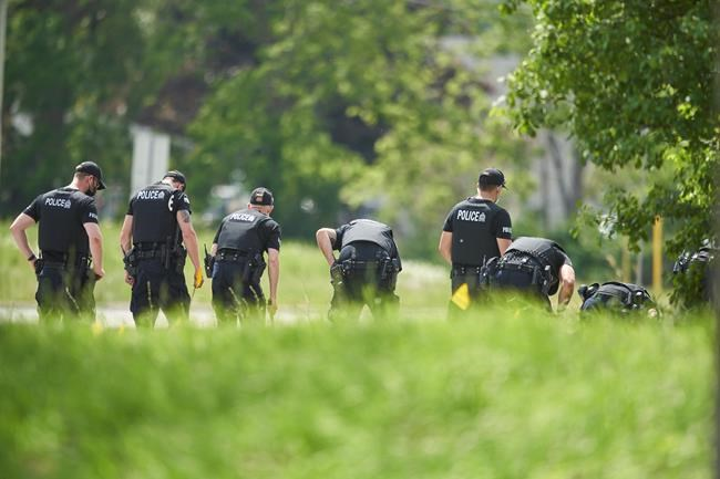 """A line of police officers look for evidence at the scene of a car crash in London, Ont., Monday, June 7, 2021. The National Council of Canadian Muslims says it is """"beyond horrified"""" by the vehicle attack, which killed four members of a family in London, Ont., Sunday. THE CANADIAN PRESS/Geoff Robins"""