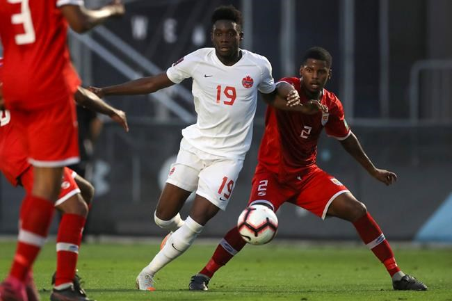 Canada's Alphonso Davies (19) breaks past Cayman Island defender Cameron Gray during the second half of a World Cup 2022 Group B qualifying soccer match Monday, March 29, 2021, in Bradenton, Fla. THE CANADIAN PRESS/AP-Mike Carlson