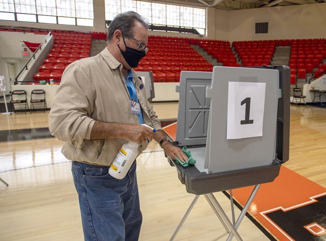 Poll worker Phil Dingus cleans one of the voting machines at the Virginia High School precinct during the Virginia Democratic Primary Election, on Tuesday, June 8, 2021, in Bristol, Va. Voter turnout though the first part of the day had been very light. (David Crigger/Bristol Herald Courier via AP)