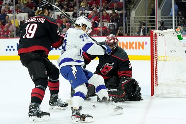 Carolina Hurricanes goaltender Alex Nedeljkovic (39) and defenseman Dougie Hamilton (19) defend against Tampa Bay Lightning center Ross Colton (79) during the first period in Game 5 of an NHL hockey Stanley Cup second-round playoff series in Raleigh, N.C., Tuesday, June 8, 2021. (AP Photo/Gerry Broome)