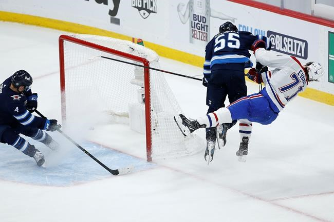 Winnipeg Jets' Mark Scheifele (55) hits Montreal Canadiens' Jake Evans (71) after he scored an empty net goal during third period NHL Stanley Cup hockey action in Winnipeg, Wednesday, June 2, 2021. THE CANADIAN PRESS/John Woods