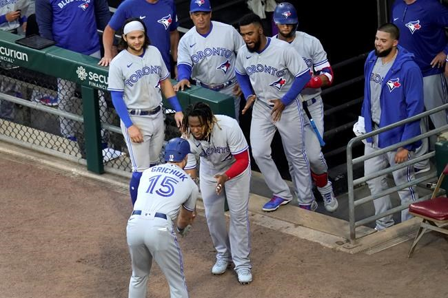 Toronto Blue Jays' Randal Grichuk celebrates his home run off Chicago White Sox starting pitcher Lance Lynn with Vladimir Guerrero Jr., as teammates watch during the second inning of a baseball game Wednesday, June 9, 2021, in Chicago. (AP Photo/Charles Rex Arbogast)