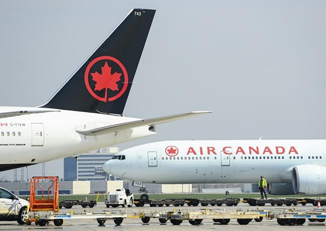 Air Canada planes sit on the tarmac at Pearson International Airport during the COVID-19 pandemic in Toronto on Wednesday, April 28, 2021. Air Canada says it will recall more than 2,600 employees who were furloughed during the COVID-19 pandemic. THE CANADIAN PRESS/Nathan Denette
