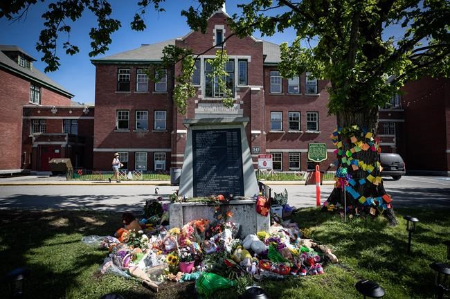 Flowers and cards are left at a makeshift memorial at a monument outside the former Kamloops Indian Residential School to honour the 215 children whose remains are believed to have been discovered buried near the city in Kamloops, B.C., on Monday, May 31, 2021. THE CANADIAN PRESS/Darryl Dyck