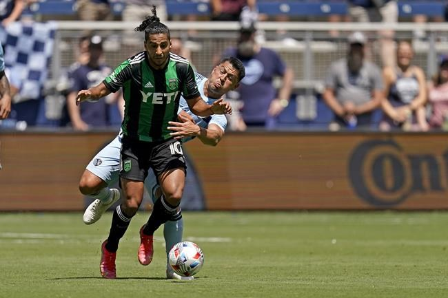 Sporting Kansas City midfielder Roger Espinoza, back, and Austin FC forward Cecilio Dominguez chase the ball during the first half of an MLS soccer match Saturday, June 12, 2021, in Kansas City, Kan. (AP Photo/Charlie Riedel)