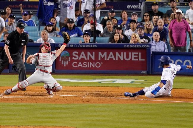 Los Angeles Dodgers' Chris Taylor, right, scores on a single by Zach McKinstry as Philadelphia Phillies catcher J.T. Realmuto, center, misses the ball while home plate umpire Ryan Wills watches during the fourth inning of a baseball game Tuesday, June 15, 2021, in Los Angeles. (AP Photo/Mark J. Terrill)