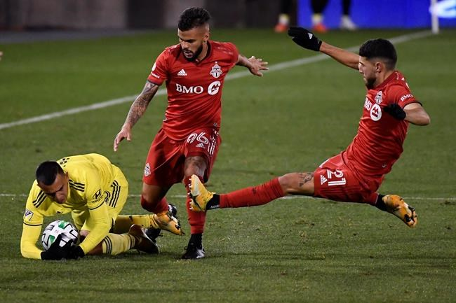 Nashville SC's Randall Leal, left, falls next to Toronto FC's Auro Jr., center, and Jonathan Osorio during the second half of an MLS soccer playoff match Tuesday, Nov. 24, 2020, in East Hartford, Conn. THE CANADIAN PRESS/AP-Jessica Hill