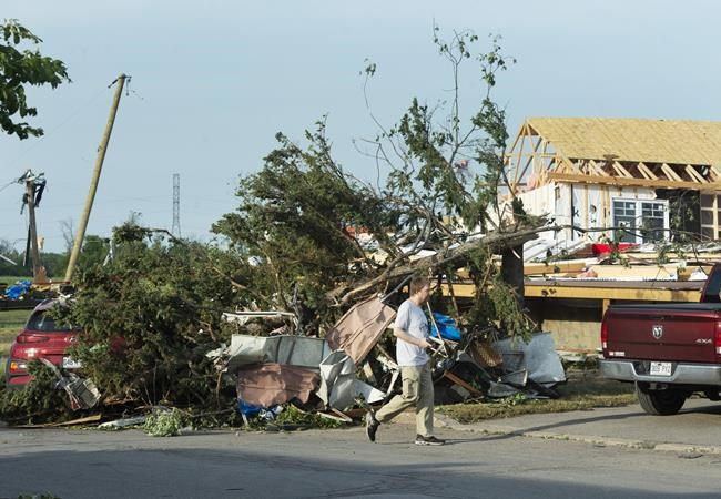 A man surveys the damage after a tornado touched down in Mascouche, Que., northeast of Montreal, Monday, June 21, 2021. Dozens of homes were damaged and one death has been confirmed. THE CANADIAN PRESS/Ryan Remiorz