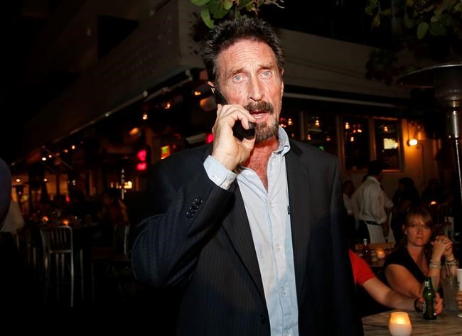 FILE - In this Dec 12, 2012 file photo, anti-virus software founder John McAfee talks on his mobile phone as he walks on Ocean Drive in the South Beach area of Miami Beach, Fla. John McAfee, the creator of the antivirus named after him, has been found dead in a cell of a jail nearBarcelona, a government source told The Associated Press on Wednesday June 23, 2021 on the same day that a Spanish court issued a preliminary ruling in favor of his extradition to the United States to face tax-related criminal charges.(AP Photo/Alan Diaz, file)