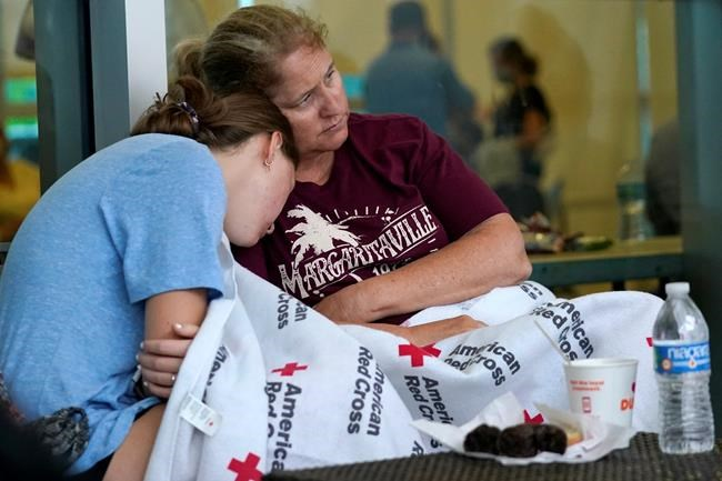 Jennifer Carr, right, sits with her daughter as they wait for news at a family reunification center, after a wing of a 12-story beachfront condo building collapsed, Thursday, June 24, 2021, in the Surfside area of Miami. Carr and her family were evacuated from a nearby building. (AP Photo/Lynne Sladky)