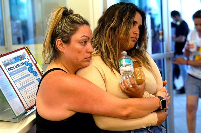 Cousins Andrea and Nellie Gonzalez wait for news at a family reunification center, after a wing of a 12-story beachfront condo building collapsed, Thursday, June 24, 2021, in the Surfside area of Miami. They are vacationing from Wisconsin and had to be evacuated from a nearby building. (AP Photo/Lynne Sladky)