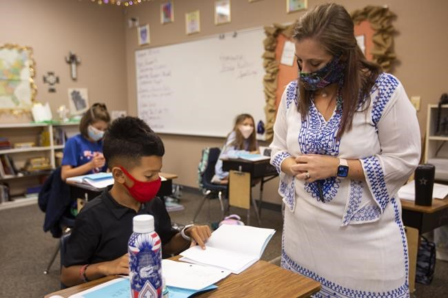FILE - Fifth-grade teacher Amanda Cardona talks with 9-year-old Ray Urias about an assignment, Tuesday, Aug. 25, 2020, in her classroom at St. John's Episcopal School in Odessa Texas. As the nation closes out a school year marred by the pandemic, some states are now starting to release new standardized test scores that offer an early glimpse at just how far students have fallen behind — with some states reporting that the turbulent year has reversed years of progress across every academic subject. (Ben Powell/Odessa American via AP)