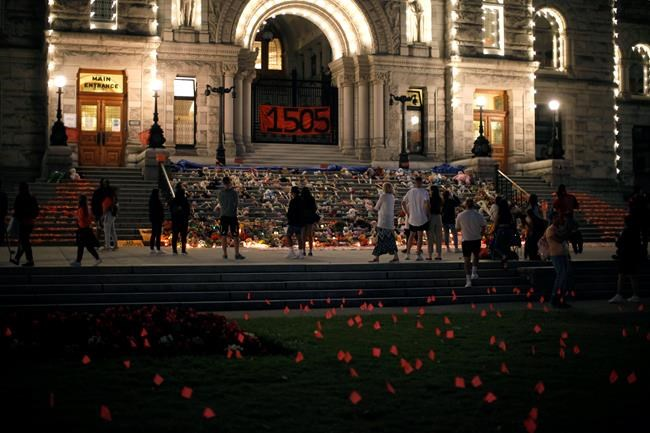 People pay respects to the victims of Canada's residential school system amid shoes, teddy bears, orange shirts and other tributes placed on the steps outside the legislature in Victoria, Thursday, July 1, 2021. THE CANADIAN PRESS/Chad Hipolito