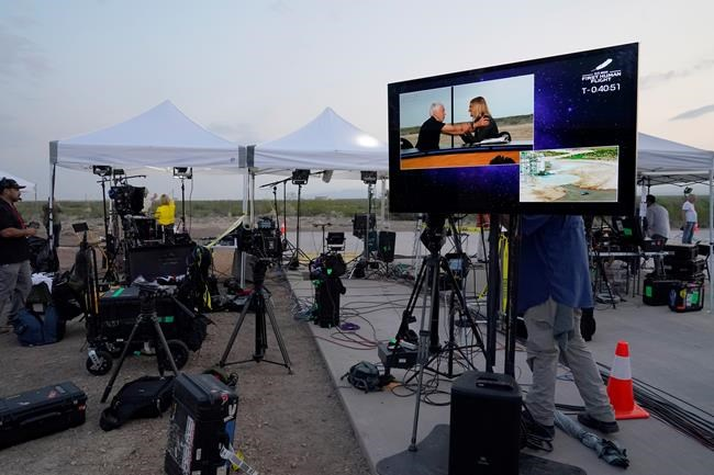 The media staging area is shown with a monitor that shows Wally Funk being interviewed near the Blue Origin's New Shepard rocket launch pad, at rear, near Van Horn, Texas, Tuesday, July 20, 2021. The rocket is scheduled to launch later this morning will carry passengers Jeff Bezos, founder of Amazon and space tourism company Blue Origin, brother Mark Bezos, Oliver Daemen and Wally Funk. (AP Photo/Tony Gutierrez)