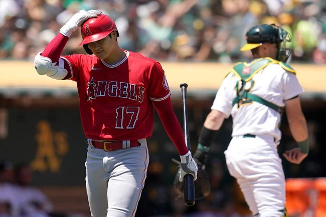 Los Angeles Angels designated hitter Shohei Ohtani (17) walks to the dugout in front of Oakland Athletics catcher Sean Murphy after striking out during the fifth inning of a baseball game in Oakland, Calif., Tuesday, July 20, 2021. (AP Photo/Jeff Chiu)