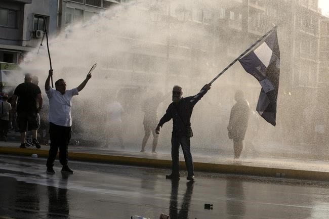 Greek police use tear gas and water cannons to disperse anti-vaccine protesters during a rally at Syntagma square, central Athens, on Wednesday, July 21, 2021. Thousands of people protested against Greek government's measures to curb rising COVID-19 infections and drive up vaccinations in the country where almost 50% of Greeks and country residents have received at least one dose of the vaccine. (AP Photo/Yorgos Karahalis)