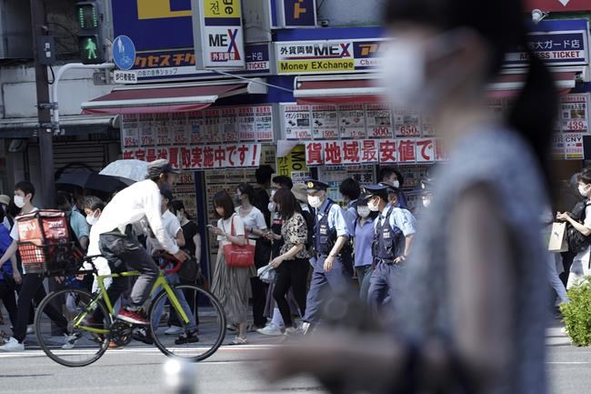 People and police officers wearing face masks to help curb the spread of the coronavirus walk past a busy crossing at Shinjuku district in Tokyo Friday, July 23, 2021, hours before the opening ceremony of the Summer Olympics starts. (AP Photo/Kantaro Komiya)