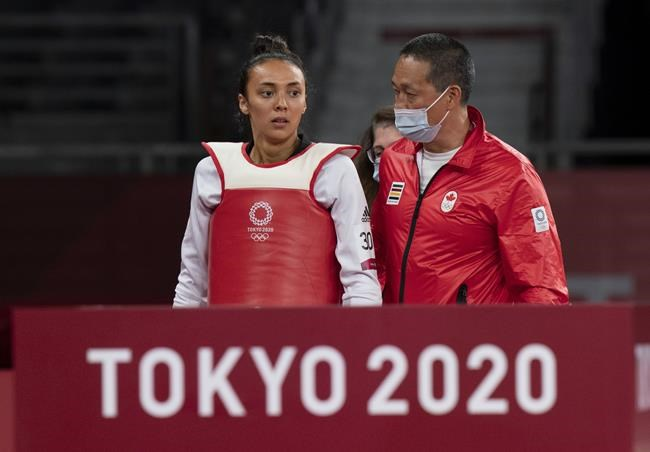 Skylar Park, from Winnipeg, Man., walks with her coach and father Jae Park after losing to Taiwan's Chia-Ling Lo in the Women's 57Kg Taekwondo quarter-final at the Tokyo Olympics, Sunday, July 25, 2021 in Chiba, Japan. THE CANADIAN PRESS/Adrian Wyld