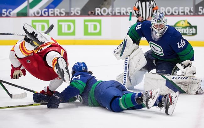 Calgary Flames' Milan Lucic, left, falls over Vancouver Canucks' Jalen Chatfield, centre, after taking a shot on goalie Braden Holtby (49) during the third period of an NHL hockey game in Vancouver, B.C., Sunday, May 16, 2021. THE CANADIAN PRESS/Darryl Dyck