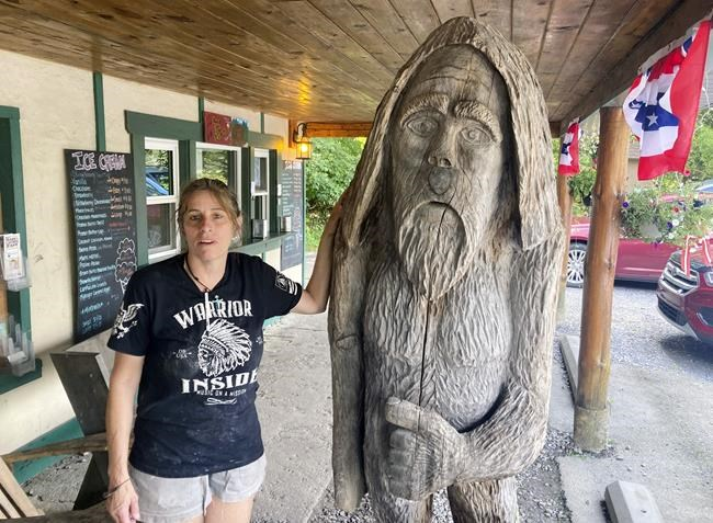 Pauline Bauer leans against a wooden statue outside Bob's Trading Post, her restaurant in Hamilton, Pa., Wednesday, July 21, 2021. Bauer is one of more than 540 people charged with federal crimes stemming from the Jan. 6 riot at the U.S. Capitol. (AP Photo/Michael Kunzelman)