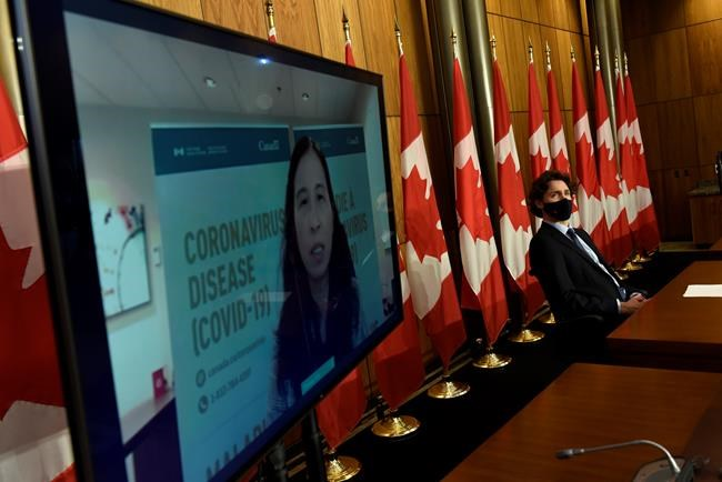 Prime Minister Justin Trudeau listens as Chief Public Health Officer of Canada Dr. Theresa Tam is seen via videoconference during a news conference on the COVID-19 pandemic in Ottawa on Friday, June 4, 2021. Federal officials are warning that Canada could be on the brink of a fourth wave of COVID-19 driven by the highly contagious Delta variant if the country opens too fast before enough people have been vaccinated. THE CANADIAN PRESS/Justin Tang