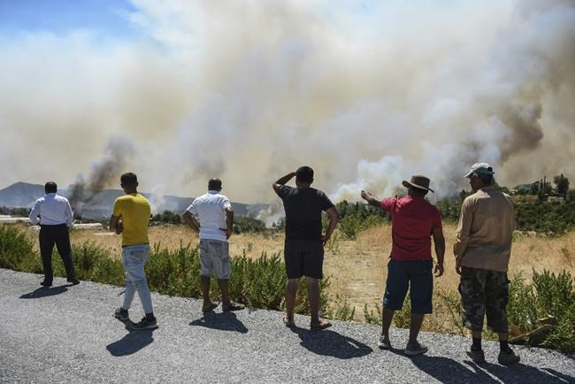 People watch wildfires in Kacarlar village near the Mediterranean coastal town of Manavgat, Antalya, Turkey, Saturday, July 31, 2021. The death toll from wildfires raging in Turkey's Mediterranean towns rose to six Saturday after two forest workers were killed, the country's health minister said. Fires across Turkey since Wednesday burned down forests, encroaching on villages and tourist destinations and forcing people to evacuate. (AP Photo)