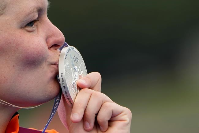 Sharon van Rouwendaal, of the Netherlands, kisses her silver medal during the victory ceremony for the women's marathon swimming event at the 2020 Summer Olympics, Wednesday, Aug. 4, 2021, in Tokyo. (AP Photo/David Goldman)