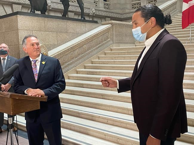 Alan Lagimodiere, left, Manitoba's minister for Indigenous reconciliation and northern relations, is confronted by Opposition NDP Leader Wab Kinew, right, shortly after being sworn into cabinet at the Manitoba legislature in Winnipeg, Thursday, July 15, 2021. Lagimodiere recently defended some of the intentions behind residential schools but now says they were part of a genocide. THE CANADIAN PRESS/Steve Lambert