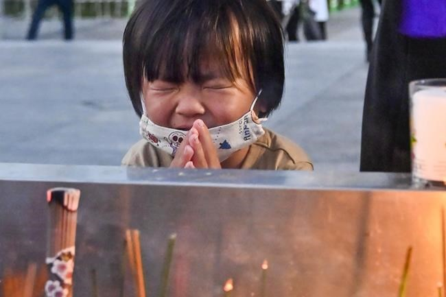 A child prays in front of the cenotaph dedicated to the victims of the atomic bombing at the Hiroshima Peace Memorial Park in Hiroshima, western Japan Friday, Aug. 6, 2021. Hiroshima on Friday marked the 76th anniversary of the world's first atomic bombing of the city. (Kyodo News via AP)