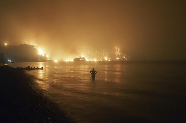 FILE - In this file photo dated Friday, Aug. 6, 2021, a man watches as wildfires approach Kochyli beach near Limni village on the island of Evia, about 160 kilometers (100 miles) north of Athens, Greece. A new massive United Nations science report is scheduled for release Monday Aug. 9, 2021, reporting on the impact of global warming due to humans. (AP Photo/Thodoris Nikolaou)