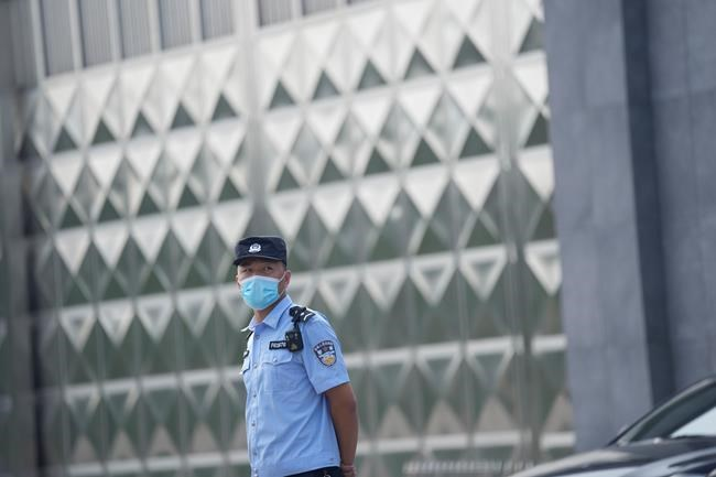 A policeman wearing a face mask stands guard outside a detention center where Dominic Barton, Ambassador of Canada to China will meet Canadian Michael Spavor, in Dandong, China, Wednesday, Aug. 11, 2021. A Chinese court has sentenced Michael Spavor to 11 years on spying charges in case linked to Huawei. (AP Photo/Ng Han Guan)