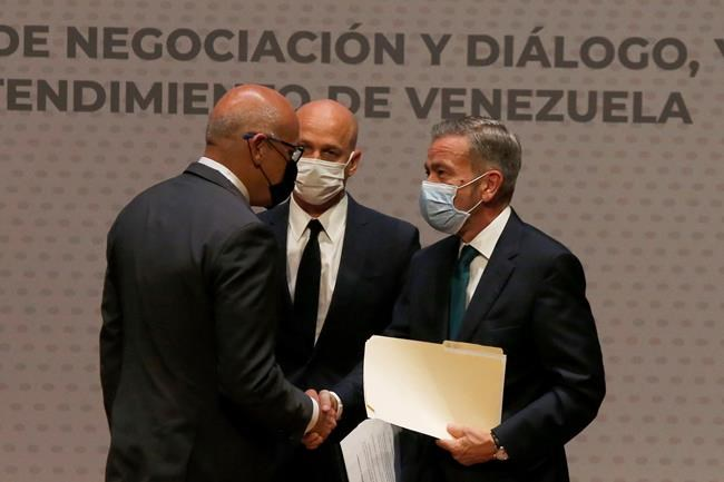 Venezuelan President of the National Assembly Jorge Rodriguez, left, shakes hands with Venezuelan opposition delegate Gerardo Blyde Perez, in Mexico City, Friday, Aug. 13, 2021. The government of Venezuela and its opposition are set to begin a new dialogue this week looking for a change in the South American nation's prolonged political standoff. (AP Photo/Marco Ugarte)