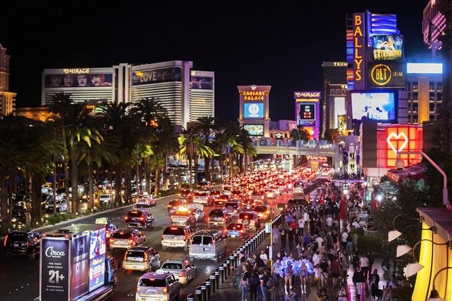 FILE - In this March 19, 2021, file photo, vehicles and crowds move along the strip in Las Vegas. The county with jurisdiction over the Las Vegas Strip has joined a legal fight to try to collect what attorneys maintain could be be hundreds of millions of dollars in unpaid hotel room taxes owed by more than 20 online travel companies. (Benjamin Hager/Las Vegas Review-Journal via AP, file)
