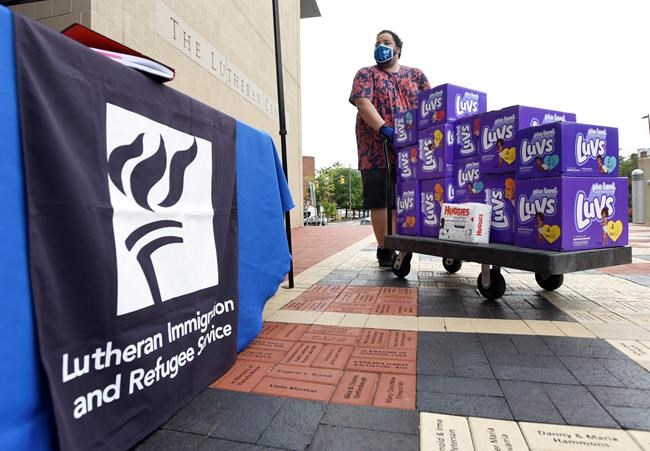 FILE - In this Tuesday, Aug. 31, 2021, file photo, Berny Lopez, an operations specialist for Lutheran Immigration and Refugee Service, moves donated diapers at the organization's drop-off site for items to help refugees from Afghanistan, in Baltimore. Many different religion groups across the U.S. are gearing up to assist the thousands of incoming refugees. (AP Photo/Steve Ruark, File)