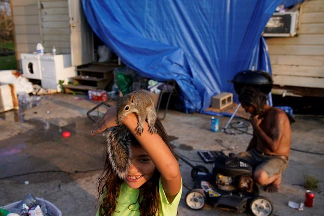 Six-year-old Mary-Louise Lacobon holds a squirrel she and her family helped after it was injured beside the home of Tommy Williams, right, in the aftermath of Hurricane Ida, Saturday, Sept. 4, 2021, in Dulac, La. (AP Photo/John Locher)