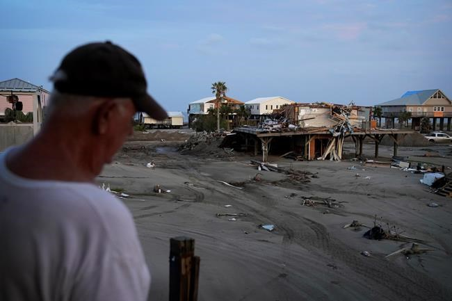 Kelty Readenour stands on his porch overlooking a sand and debris-covered roadway and homes destroyed by Hurricane Ida, Monday, Sept. 6, 2021, in Grand Isle, La. (AP Photo/John Locher)