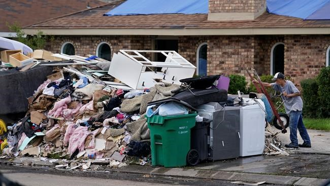 A resident dumps debris while gutting his flooded home in the aftermath of Hurricane Ida in LaPlace, La., Tuesday, Sept. 7, 2021. (AP Photo/Gerald Herbert)