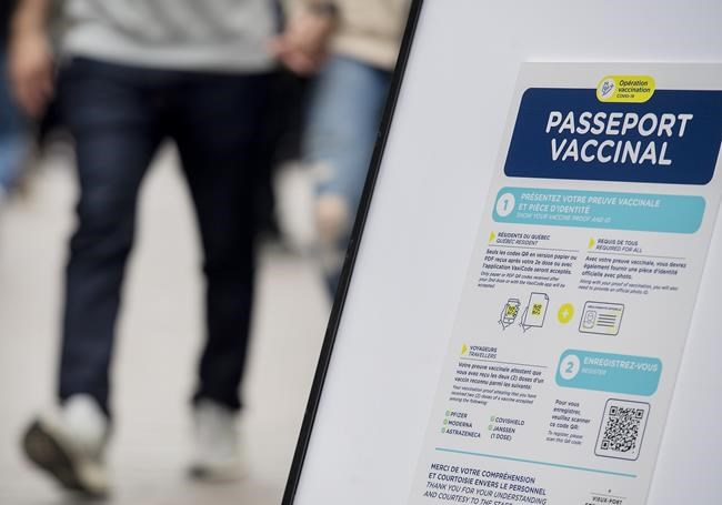 People walk by a sign at a restaurant advising customers of Quebec's newly implemented Covid-19 vaccine passport in Montreal, Monday, Sept. 6, 2021. THE CANADIAN PRESS/Graham Hughes