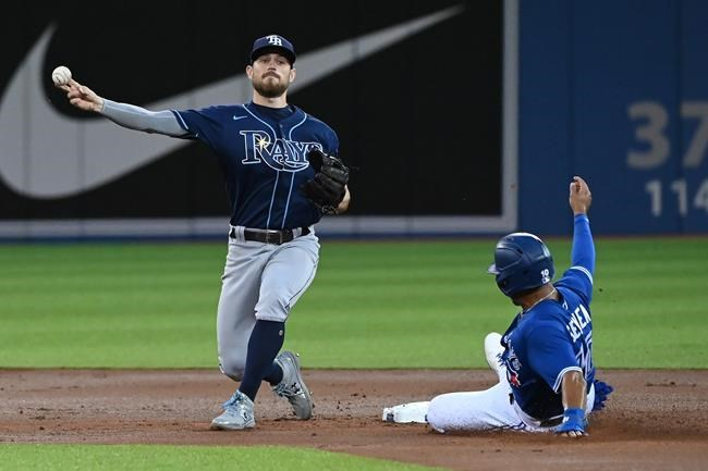 Tampa Bay Rays' Brandon Lowe, left, forces out Toronto Blue Jays' Marcus Semien at second base and throws to to first base to complete a double play on a ball hit by Blue Jays' Vladimir Guerrero Jr. in the first inning of an American League baseball game in Toronto on Tuesday, Sept. 14, 2021. THE CANADIAN PRESS/Jon Blacker