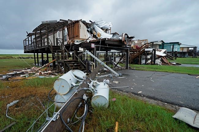 Storm clouds from approaching Tropical Storm Nicholas are seen behind homes destroyed by Hurricane Ida, in Pointe-aux-Chenes, La., Tuesday, Sept. 14, 2021. (AP Photo/Gerald Herbert)