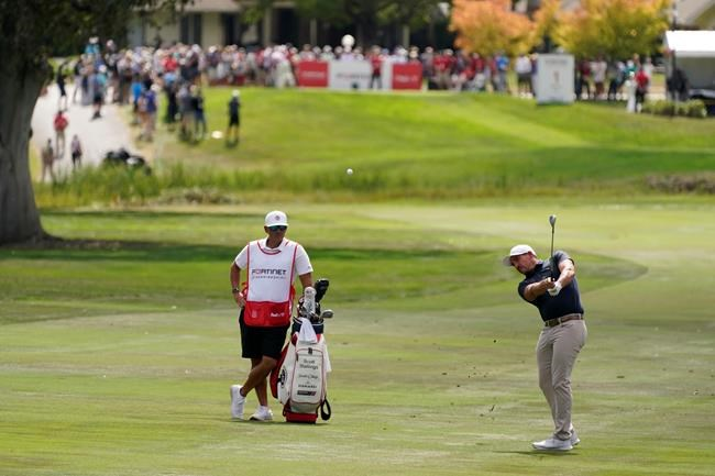 Scott Stallings, right, hits his approach shot from the first fairway of the Silverado Resort North Course during the final round of the Fortinet Championship PGA golf tournament Sunday, Sept. 19, 2021, in Napa, Calif. (AP Photo/Eric Risberg)