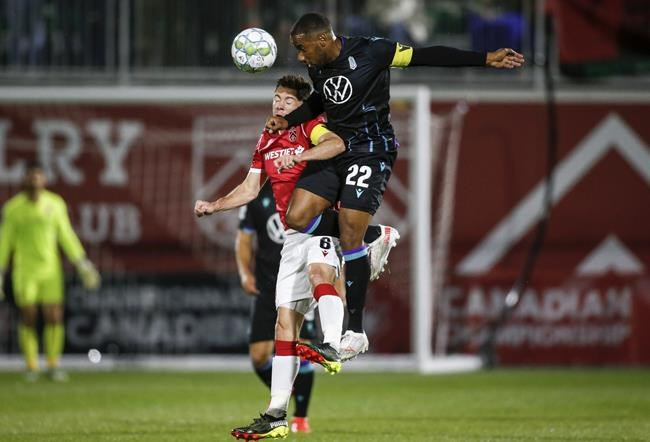 Pacific FC's Jamar Dixon, right, battles for the ball with Cavalry FC's Nik Ledgerwood during first half soccer action in the Canadian Championship quarterfinal in Calgary, Alta., Wednesday, Sept. 22, 2021.THE CANADIAN PRESS/Jeff McIntosh