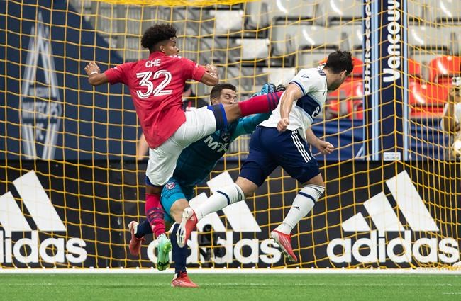 Vancouver Whitecaps' Brian White, front right, scores against FC Dallas goalkeeper Jimmy Maurer, back, as Justin Che defends during the first half of an MLS soccer game in Vancouver, on Saturday, September 25, 2021. THE CANADIAN PRESS/Darryl Dyck
