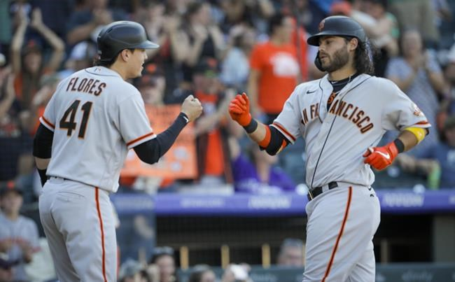 San Francisco Giants' Wilmer Flores (41) congratulates Brendan Crawford after Crawford's three-run home run in the ninth inning of a baseball game against the Colorado Rockies in Denver, Sunday, Sept. 26, 2021. San Francisco won 6-2. (AP Photo/Joe Mahoney)