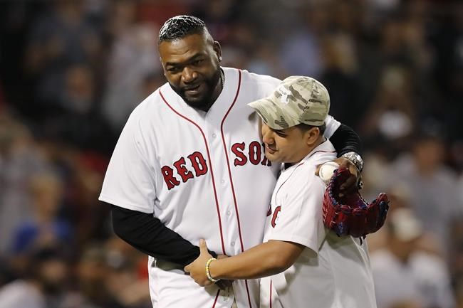 Former Boston Red Sox's David Ortiz, left, hugs Yolbin Rosario after Rosario threw out the ceremonial first pitch before a baseball game against the New York Yankees, Sunday, Sept. 26, 2021, in Boston. Rosario is the brother of Sgt. Johanny Rosario Pichardo, a U.S. Marine who was among 13 service members killed in a suicide bombing in Afghanistan. (AP Photo/Michael Dwyer)