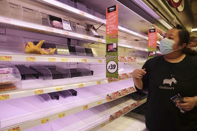 A woman looks at the empty shelves at a supermarket as she shops for food in preparation for the approaching Tropical Storm Kompasu in Hong Kong Tuesday, Oct. 12, 2021. The Hong Kong Observatory issuing the number 8 signal as Severe Tropical Storm Kompasu edges closer to the city. (AP Photo/Vincent Yu)