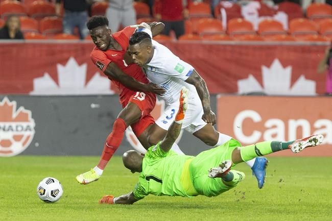 Canada's Alphonso Davies (left) runs around Panama goalkeeper Luis Mejia as Harold Cummings defends during first half World Cup qualifying action in Toronto, on Wednesday, October 13, 2021. THE CANADIAN PRESS/Chris Young