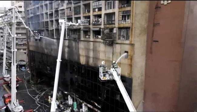 In this image taken from video by Taiwan's EBC, firefighters shoot water into a building that caught fire in Kaohsiung, in southern Taiwan on Thursday, Oct. 14, 2021. The fire engulfed a 13-story building overnight in southern Taiwan, the island's semi-official Central News Agency reported Thursday. (EBC via AP )