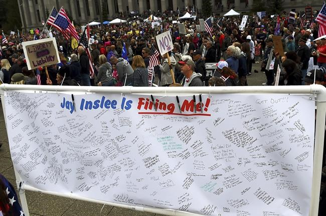 A banner filled with signatures of state employees who may lose their jobs after the Oct. 4 deadline requiring their full vaccination stands on display as people fill the Capitol campus in Olympia, Wash., Sunday, Oct. 3, 2021, to rally against the COVID-19 vaccination mandate by Gov. Jay Inlsee. (Steve Bloom/The Olympian via AP)